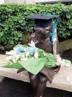 開心的畢業生忍不住與「閱讀的少女」分享喜悅之情,為她戴上學士帽,還獻花給她,邀她為畢業的見證者。(圖�劉瀚之)