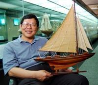 第70萬位造訪海博館幸運兒,為本校校醫兼組長談遠安,捧著船身長40公分、高30公分的「奮勇號」開心的笑。(陳振堂攝)