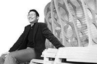 陳宏銘坐在自己設計的作品上,自信地微笑。(攝影�林奕宏)
