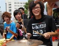 「嘿!就是你!快來加入我們吧!」西洋音樂社社員打鼓、彈奏樂器炒熱氣氛,抓住同學好奇目光。(下圖�黃士航)