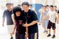 排球課堂上,老師正在傳授同學如何拉筋,和同學笑鬧成一片。(圖�陳振堂)