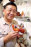 商館3F酒文化研究室,「寶瓶齋」主持人何永成,捧著「八仙過海」造型酒瓶,提早在校慶前亮相,這可是心肝寶貝呢!(記者邱湘媛攝)