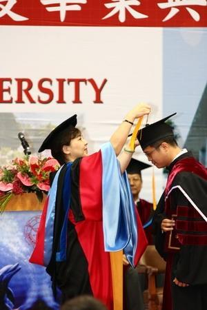 校長張家宜在畢業典禮上,親自為博士班畢業生撥穗,並頒發畢業證書。(圖�王家宜)