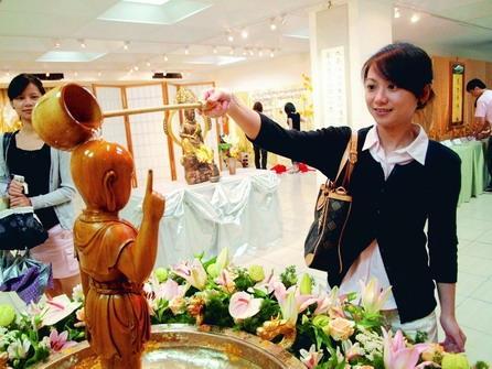 正智佛學社上週在商管展示廳舉辦浴佛祈福活動,上圖女學生正在浴佛,洗滌佛像身上的塵垢。(攝影�劉瀚之)