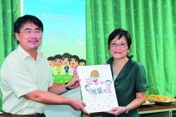 新任文學院院長邱炯友(左)代表文學院同仁,送給卸任院長趙雅麗一張寫滿祝福的卡片。(圖�&#20931嘉翔)