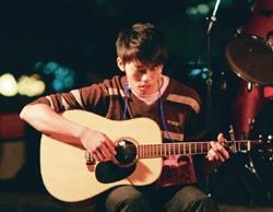 吉他社日前舉辦戶外民歌演奏,表演者在台上彈得認真,台下觀眾也聽得忘我。(攝影�洪翎凱)