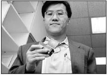 圖為機電系教授康尚文手持其研發作品「平板式迴路熱管」的原型,康尚文據此研發製造出更高技術的第6代「平板式迴路熱管」,並成功技術轉移,將由產學合作廠商進行量產。