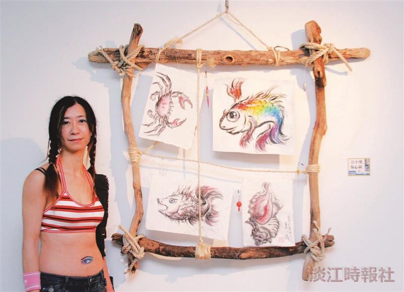 淡水在地藝術家百件作品聯展聯誼茶會,藝術家吳心荷與她的作品「淡水情」合影。