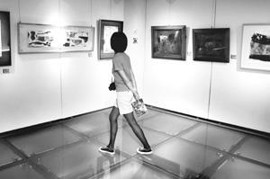 文錙藝術中心現展出「今日有約」畫展,徜徉其中的她,正仔細品嘗繪畫之美。