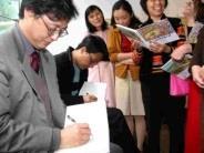 參與漫畫展開幕典禮的漫畫家們,受到本校師生的熱倩包圍,忙著在本次漫畫展發行的專冊上簽名留念。(記者陳震霆攝)