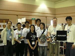 本校人型機器人組的五位同學與翁慶昌教授(左一)、加拿大隊指導老師(右二),以及加拿大隊學生代表(左二),於比賽會場中合影留念。(電機系提供)