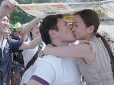 東南亞所翁履中同學在烈日下抱著女友親吻一個小時,挑戰一萬元獎金,親友團在一旁加油打氣,還用報紙幫忙遮陽。(攝影�昂力)