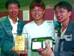 冠軍作品「利用指紋影像實現個人身分辨識系統」 的得獎團隊高興的展示出獎牌及作品,大聲歡呼:「We are winners!」由左至右為劉哲瑋、林家慶與李建潁。(攝影�昂力)