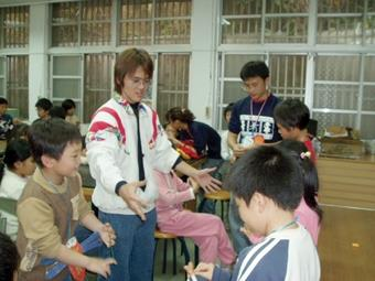 嘉雲校友會利用寒假,前往文光國小舉辦認識台灣之美營隊,數學一呂明昇(左二)扮演「陳嘴扁」,教同學變魔術,深獲小朋友喜愛。(嘉雲校友會提供)