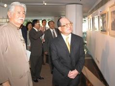 創辦人張建邦(圖右)聽取文錙藝術中心主任李奇茂(左)解說展出的藝術品。(攝影/陳國良)