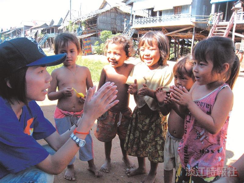 柬埔寨服務學習團於暑假期間前往柬埔寨開設中文和電腦的課程。圖為服務員與當地孩童互動情形(圖/課外組提供)